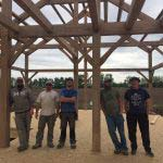 5 men standing inside a timber frame structure they have just completed raising