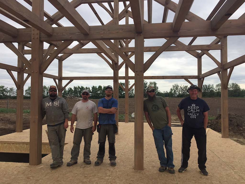 5 timber framers standing under timber frame house
